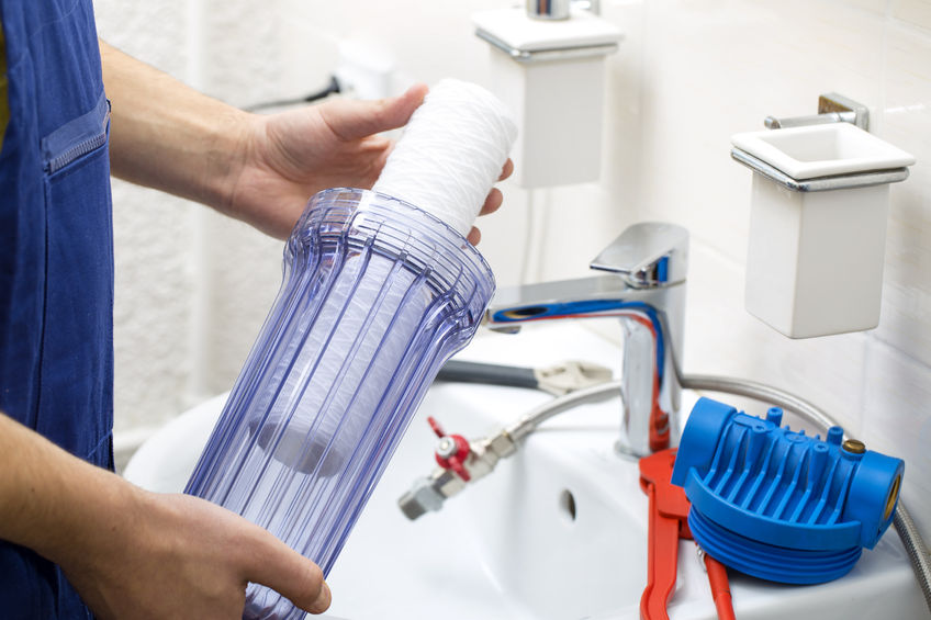 56598411 - plumber installing new water filtration system