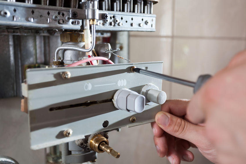 Plumber fixing a gas water heater with screwdriver